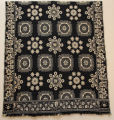 "Dark blue and white double jacquard coverlet with 2 trade blocks, dated 1852. Bottom border is grapevine while side borders are large flowers. Top is hemmed. Bottom has self-fringe, approx. 4 1/2"". Field pattern has tiles alternating with floral medallions."