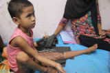 Child receiving treatment sits with her mother in medical clinic